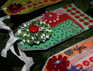 "Hand-made tags with paper ""yo-yo"" flower added."